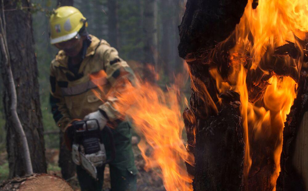 يقوم موظفو أفيا ليسو أوخرانا  لحراسة الغابات بمكافحة الحرائق لمنع انتشارها على نطاق أوسع في ياقوتيا، روسيا 11 يوليو 2021
