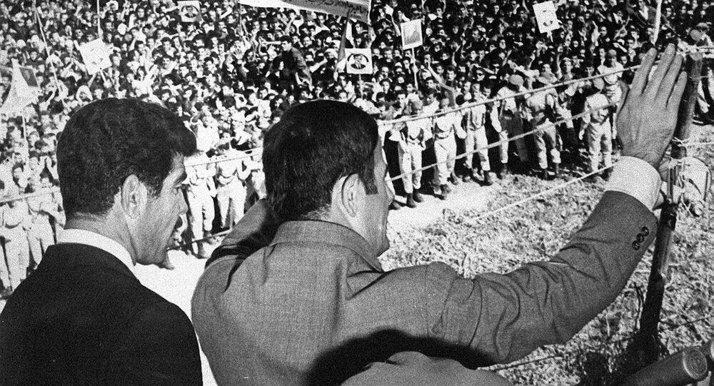 صورة غير مؤرخة تظهر الرئيس السوري حافظ الأسد (إلى اليمين) وهو يحيي الحشود في دمشق. يقف إلى جانبه الرئيس العراقي صدام حسين.