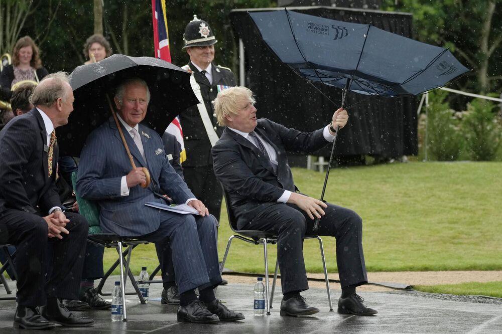 الأمير تشارلز، وسط الصورة، ورئيس الوزراء بوريس جونسون، إلى اليمين، يحتميان من المطر أثناء إزاحة الستار عن النصب التذكاري لشرطة المملكة المتحدة في بستان النصب التذكاري الوطني في ألريواس، إنجلترا، 28 يوليو 2021