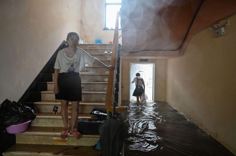 أشخاص في فندق غمرته المياه في مدينة نينغبو بمقاطعة تشجيانغ شرقي الصين، حيث ضرب إعصار إن-فا الساحل الشرقي للصين،  25 يوليو 2021