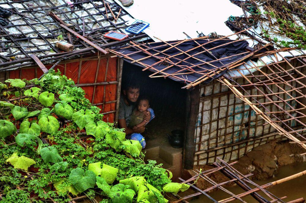 لاجئ من الروهينغا يجلس مع طفله داخل مأواه الذي غمرته المياه بعد هطول أمطار غزيرة في مخيم الروهينغا للاجئين في كوتوبالونغ، بنغلاديش، 28 يوليو  2021