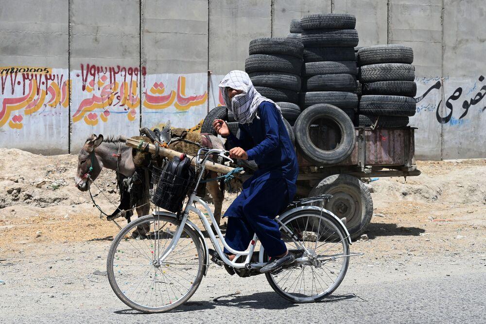 شاب يركب دراجة هوائية بجوار عربة تجرها الحمير المحملة بالإطارات في كابول، أفغانستان 27 يوليو 2021