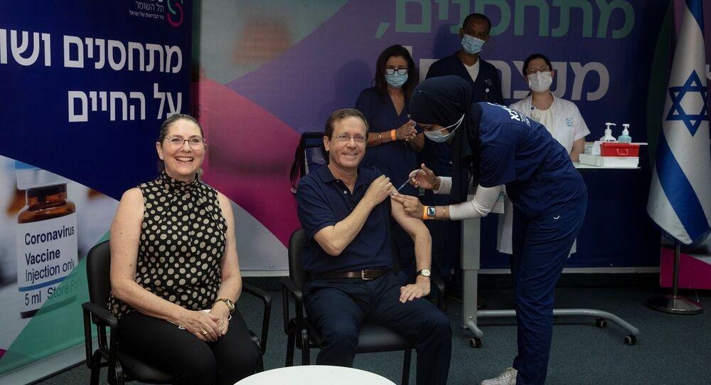 الرئيس الإسرائيلي، إسحاق هرتسوغ، وزوجته، أثناء تلقيهما جرعة ثالثة من لقاح فيروس كورونا المستجد، 30 يوليو/ تموز 2021