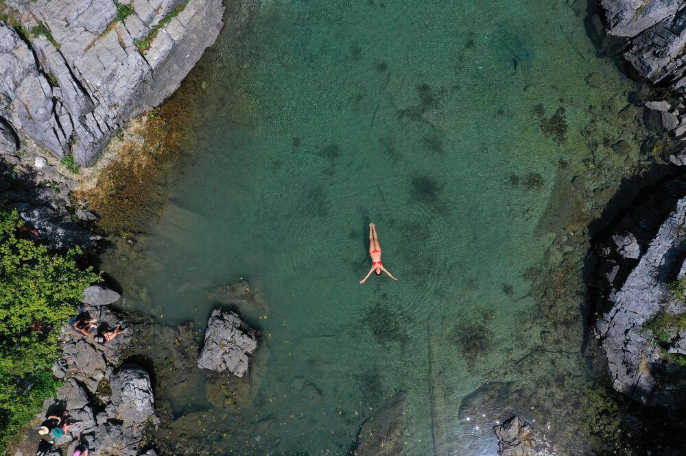 امرأة تسبح لتبرد في بحيرة كسيما، وهي بحيرة طبيعية صغيرة تقع في حديقة فالبونا الوطنية بالقرب من دراغوبي، 4 أغسطس 2021