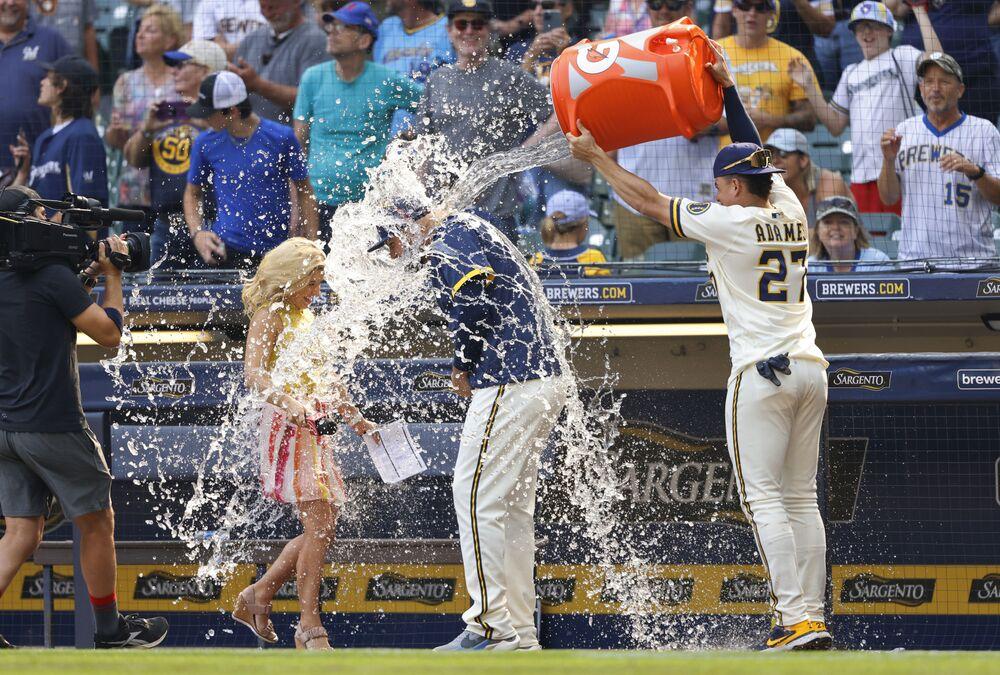 ويلي آدامز (27) من ميلووكي برورز يصب الماء على زميله في الفريق رودي تيليز خلال مقابلة بعد فوز فريق برورز على بيتسبرغ بايرتس في مباراة بيسبول، ميلووكي، 4 أغسطس 2021 . ضرب تيليز شوطًا ثلاثيًا متضررًا خلال الشوط السابع.