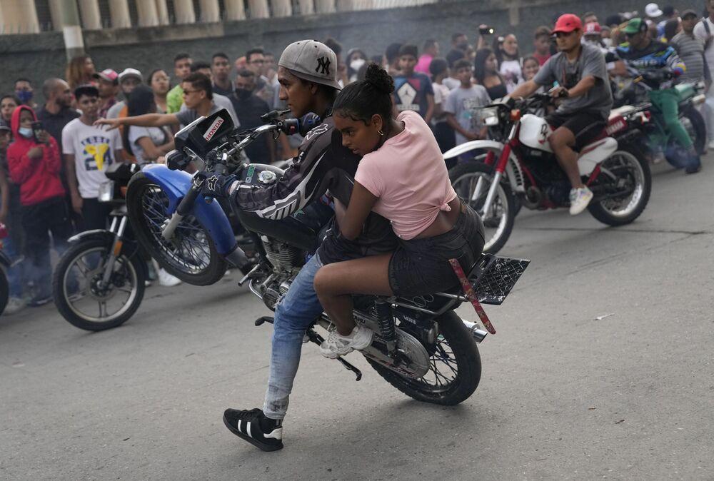 يقوم سائق دراجة نارية بحركة بهلوانية على دراجته النارية مع أحد الركاب خلال معرض في حي إل فالي في كاراكاس ، فنزويلا ، 31 يوليو 2021