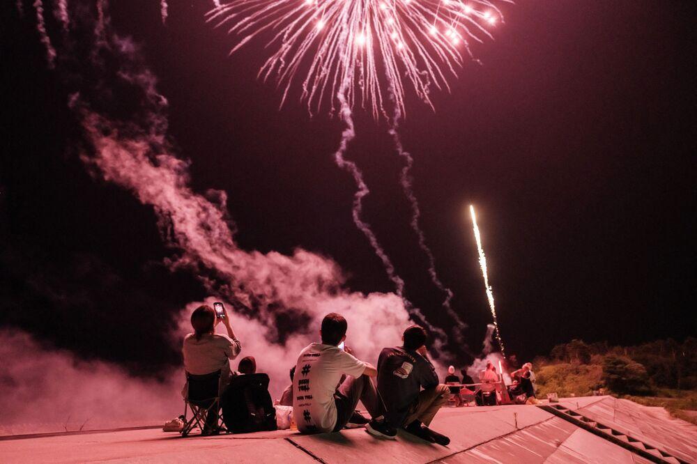 الناس يشاهدون الألعاب النارية على جدار بحري أعيد بناؤه بعد وقوع كارثة تسونامي في عام 2011، في ميناميسوما، محافظة فوكوشيما، اليابان 1 أغسطس 2021