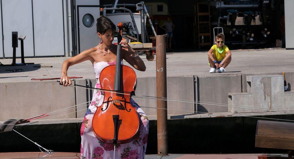 فنانة تعزف على آلة التشيلو على متن قارب على شكل كمان بعنوان كمان نوح  أثناء رحلة تجريبية في مدينة البندقية، إيطاليا، 6 أغسطس/ آب 2021