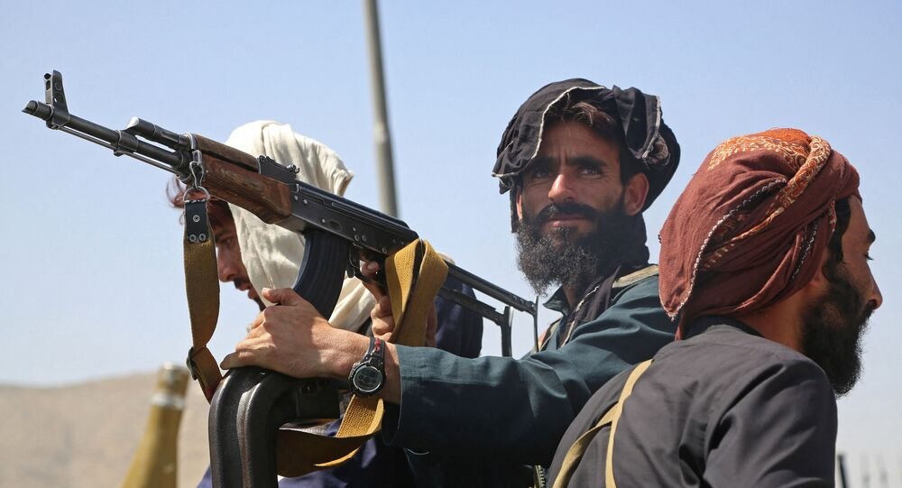 مسلحي حركة طالبان على متن مركبة أثناء مرورهم في العاصمة كابول إثر السيطرة عليها في 15 أغسطس 2021