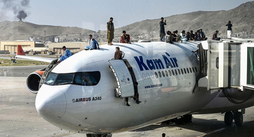 أفغان يتسلقون طائرة في مطار كابول