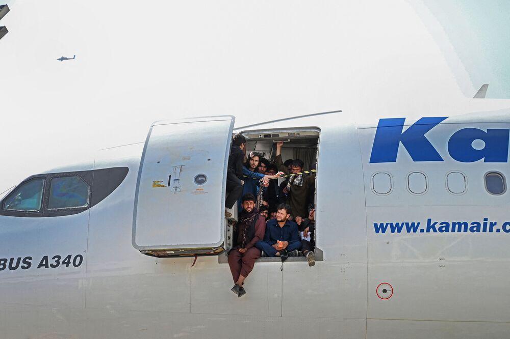 أفغان يجلسون على باب طائرة في مطار كابول
