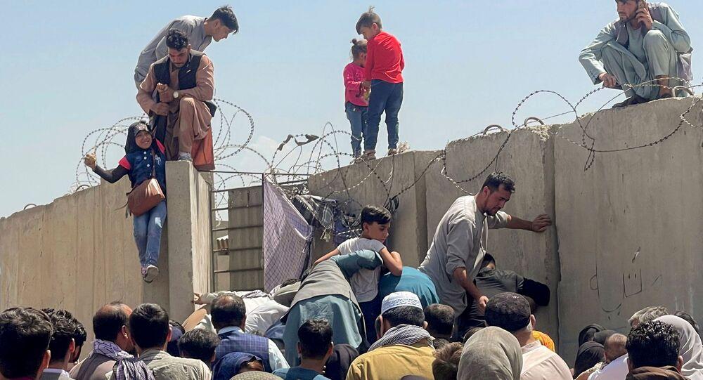 رجل يرفع فتاة إلى أعلى السور في مطار كابول