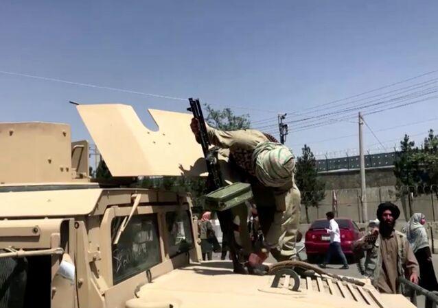 مقاتل من طالبان  يثبت رشاشا على ناقلة جند مدرعة بالقرب من مطار كابول