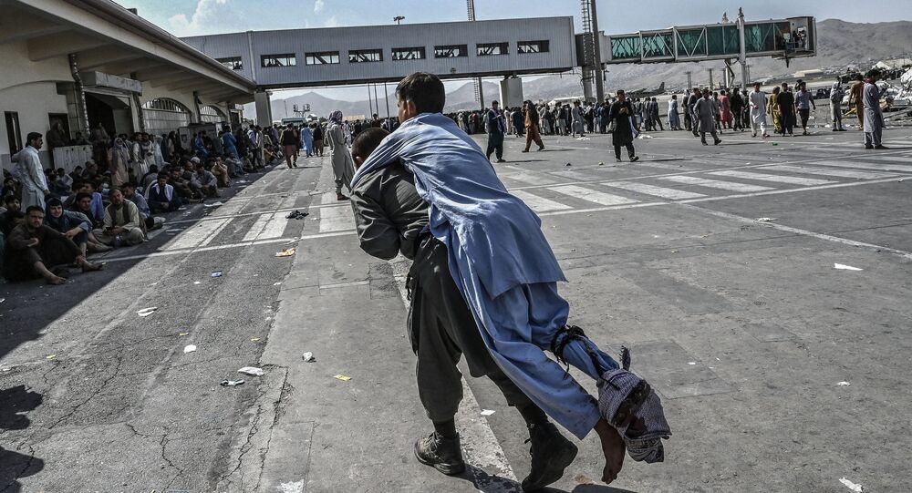 متطوع ينقل جريح أفغاني في مطار كابول
