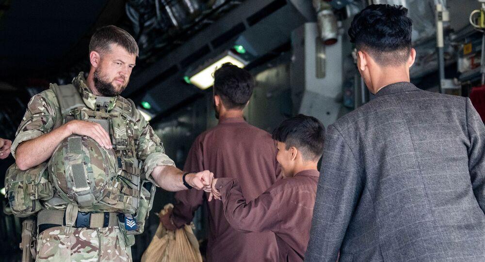 جندي بريطاني ومواطنون أفغان  من مطار كابول