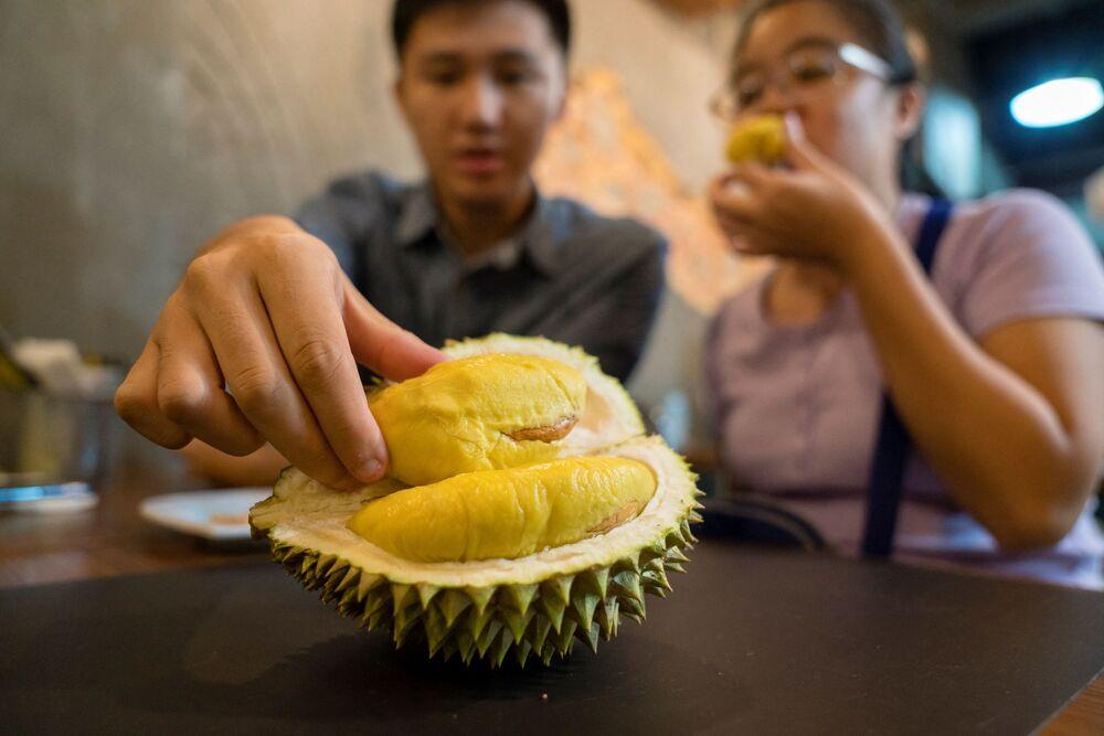 أحد الزبائن يتذوق  الفاكهة الاستوائية اللاذعة دوريان في مقهى ماو شان وانغ في سنغافورة.