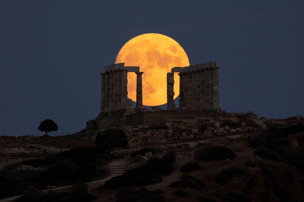 اكتمال القمر فوق معبد بويسدون في كيب سونيون بالقرب من مدينة أثينا، اليونان 21 أغسطس 2021