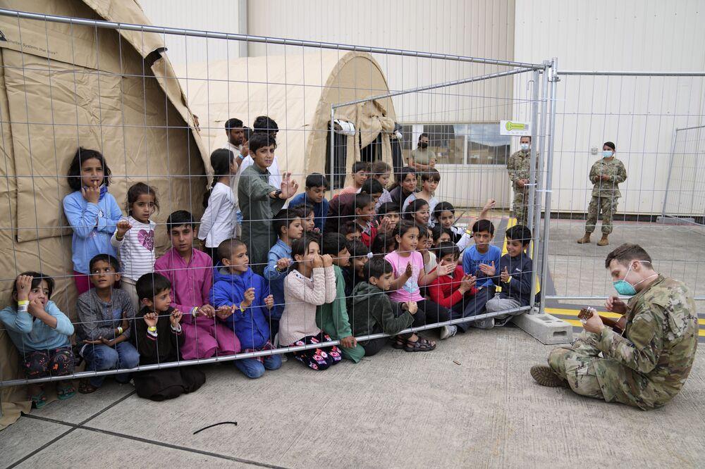 جندي أمريكي يعزف على الغيتار لأطفال أفغانيين تم إجلاءهم من أفغانستان إلى القاهعدة الجوية رامشتين في ألمانيا 24 أغسطس 2021