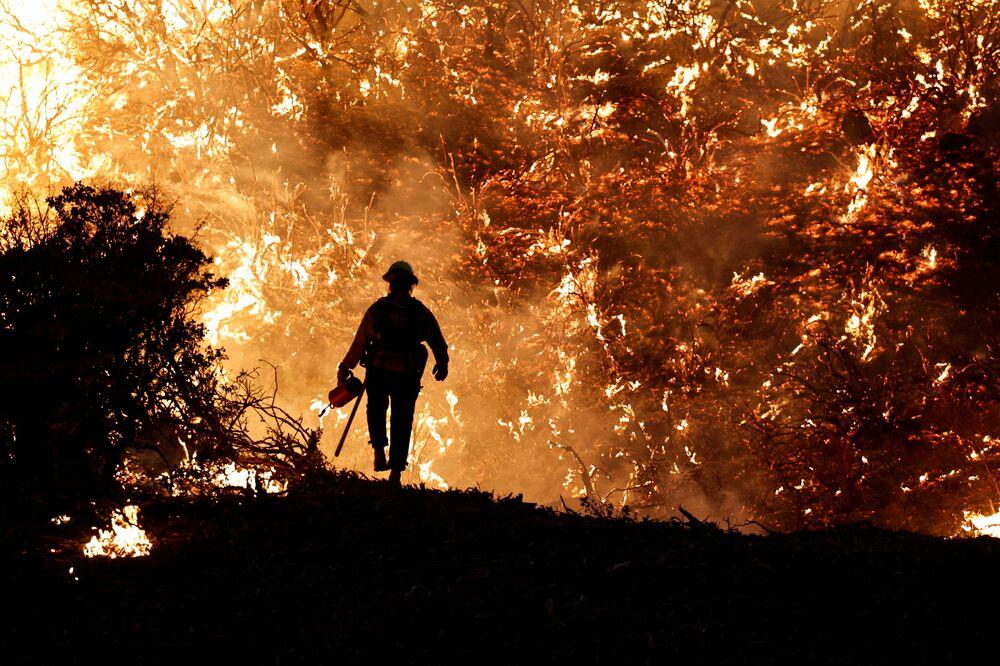 رجل إطفاء يسير على خلفية اشتعال حريق كالدور في جريزلي فلاتس، ولاية كاليفورنيا، الولايات المتحدة 22 أغسطس 2021