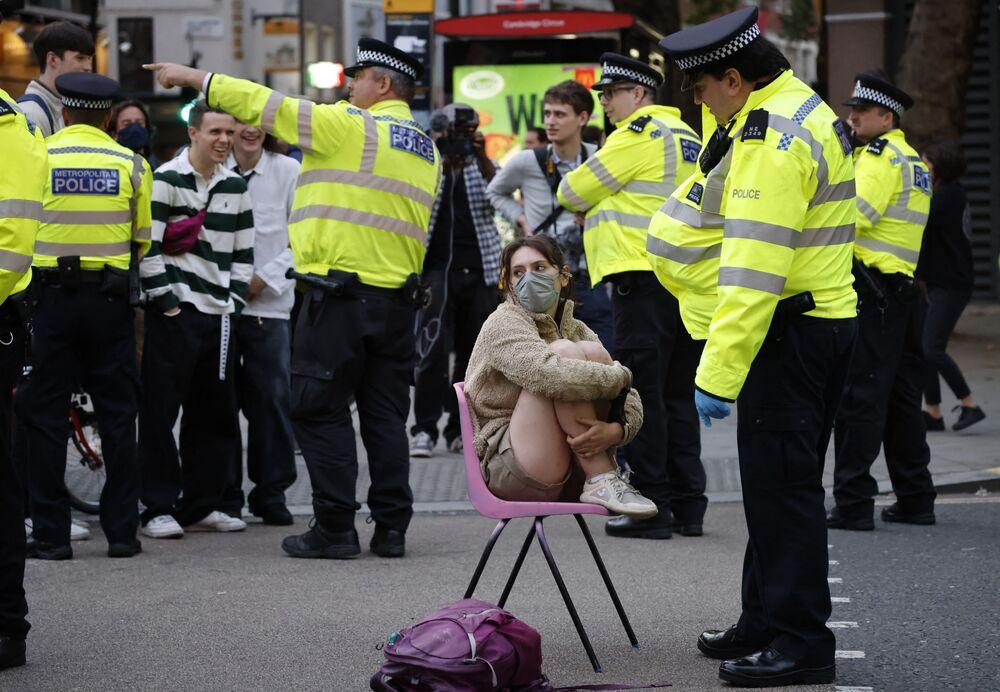 ضابط شرطة يتحدث إلى ناشط مناخي من جماعة تمرد ضد الانقراض وسط لندن، بريطانيا 24 أغسطس 2021 خلال سلسلة أعمال المجموعة التمرد المستحيل''.