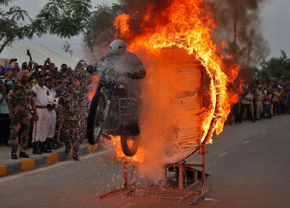 جندي من قوة حراسة الحدود ينفذ حركة بلهوانية على دراجته النارية خلال عرض على الطريق للاحتفال بمرور 75 عامًا على استقلال الهند، في أحمد أباد، الهند، 25 أغسطس 2021
