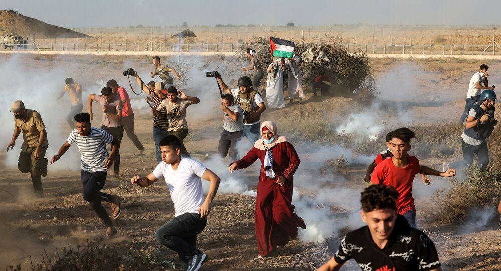 متظاهرون فلسطينيون وصحفيون يفرون من قنابل غاز المسيلة للدموع على حدودو قطاع غزة، فلسطين 25 أغسطس 2021