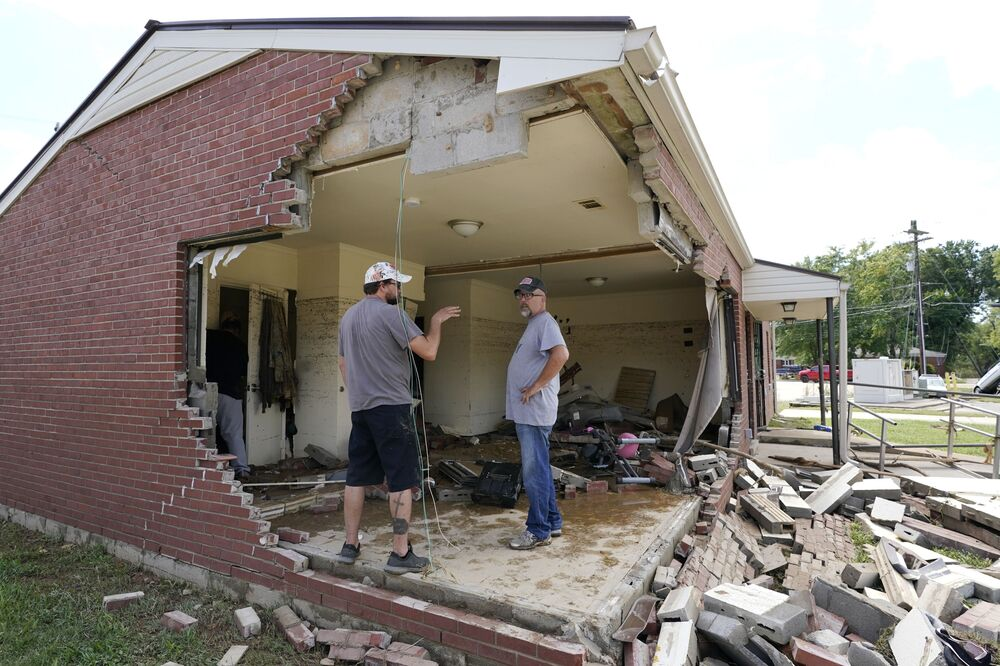 بريان ميتشل (يمين الصورة)  ينظر من خلال منزل حماته المتضرر مع صديق العائلة كريس هوفر (يسار الصورة) في ويفرلي، ولاية تينيسي، الولايات المتحدة، 22 أغسطس 2021