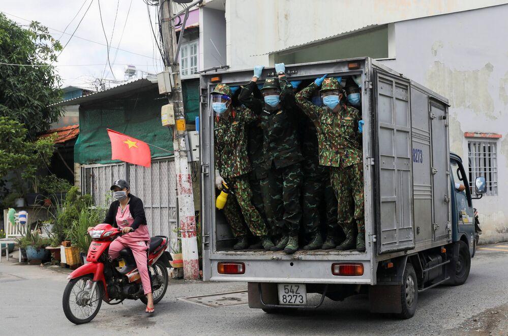 جنود فيتناميون ينظرون من شاحنة وهم يسلمون الطعام في مناطق مغلقة مشددة وسط جائحة فيروس كورونا (كوفيد-19) في هوشي منه، فيتنام، 24 أغسطس 2021