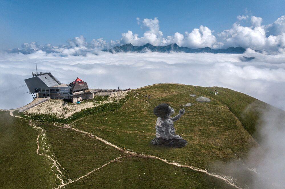 صورة جوية التقطت في 24 أغسطس 2021 على قمة جبل مولسون في سويس بريلبس، مطلة على منطقة غرويريس، تظهر لوحة جدارية عملاقة للفنان الفرنسي غيوم ليغروس، المعروف باسم سايبي، بعنوان: نفس جديد يمثل الصبي تهب الغيوم.