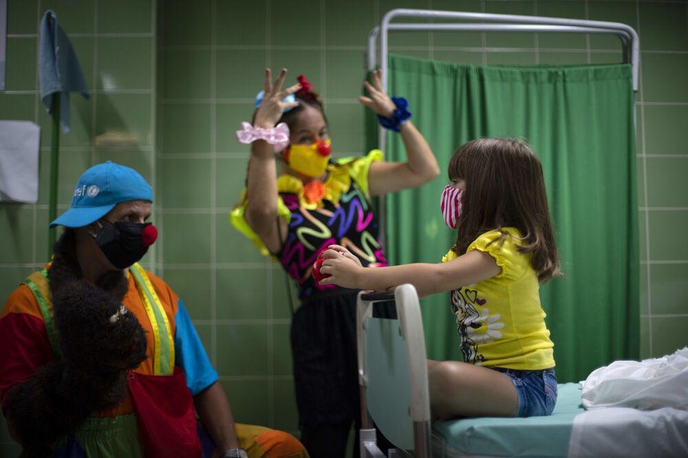 المهرجون يقومون بترفيه فتاة أثناء انتظارها في غرفة التمريض بعد حقنها بجرعة من لقاح سوبيرانا-02 ضد كوفيد-19 في هافانا، كوبا،  24 أغسطس 2021