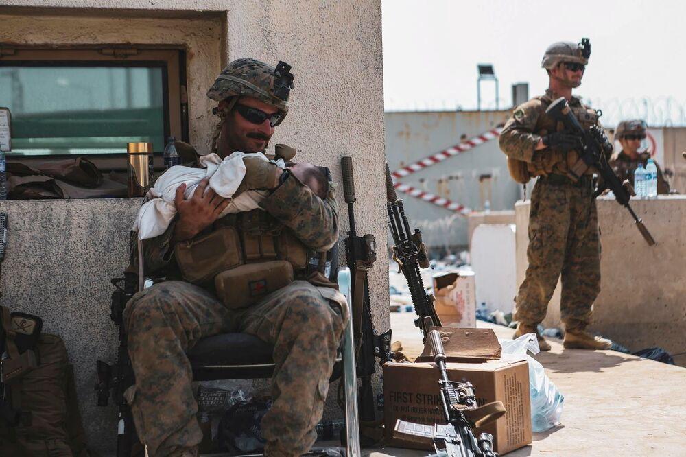 جندي من مشاة البحرية الأمريكية تم تعيينه في الوحدة الاستكشافية البحرية الرابعة والعشرين، يحمل طفلاً أثناء عملية إجلاء الأفغانيين في مطار حامد كرزاي الدولي في كابول، أفغانستان، 20 أغسطس 2021
