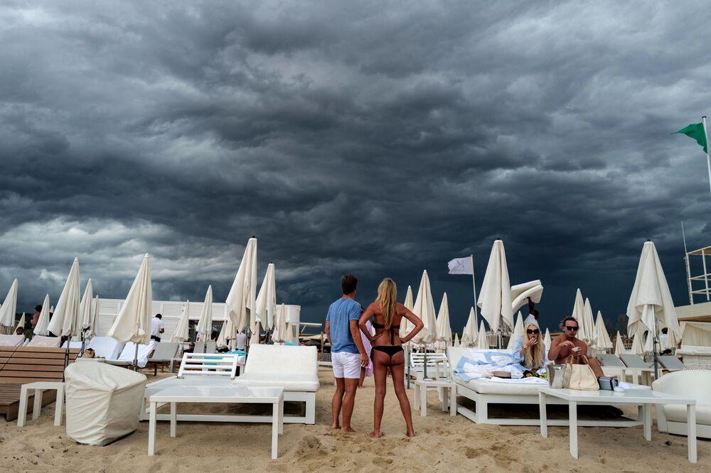 ينظر الناس إلى السحب السوداء أثناء وقوفهم على شاطئ في راماتويل، بالقرب من سان تروبيه، جنوب فرنسا 24 أغسطس 2021