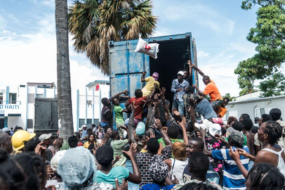 رجل يلقي بكيس أرز وسط حشد من الناس أثناء توزيع الطعام والماء على ضحايا الزلزال في لو كواي، هايتي 20 أغسطس 2021