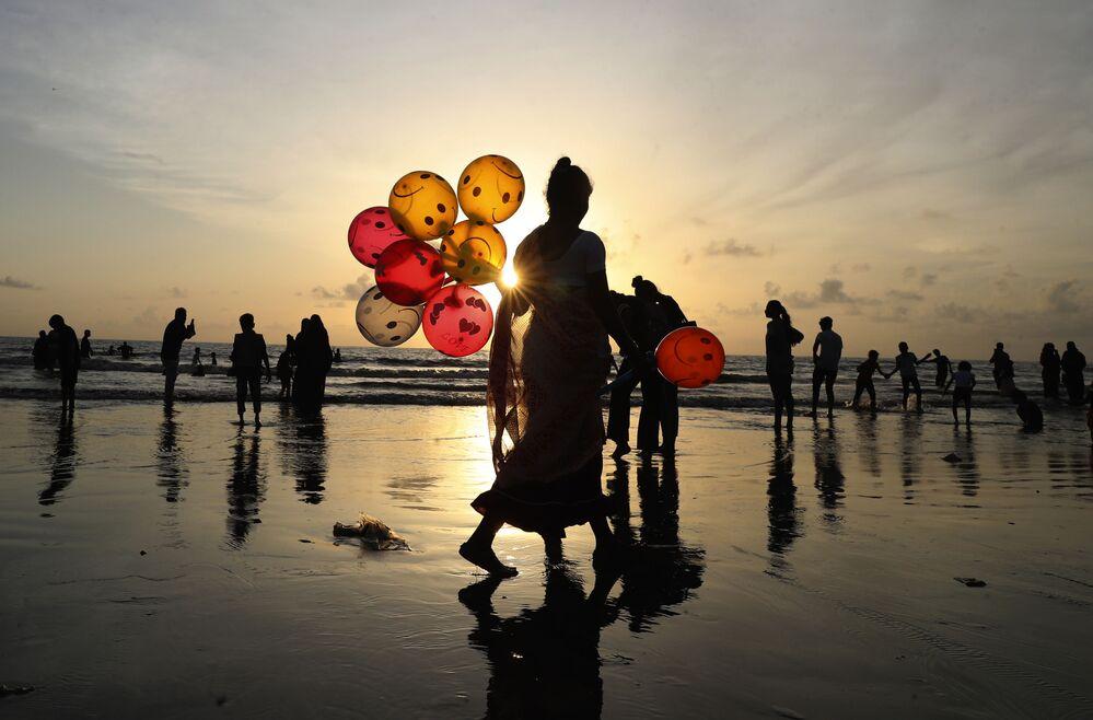 امرأة تبيع البلالين على شاطئ جوهو في مومباي، الهند 24 أغسطس 2021