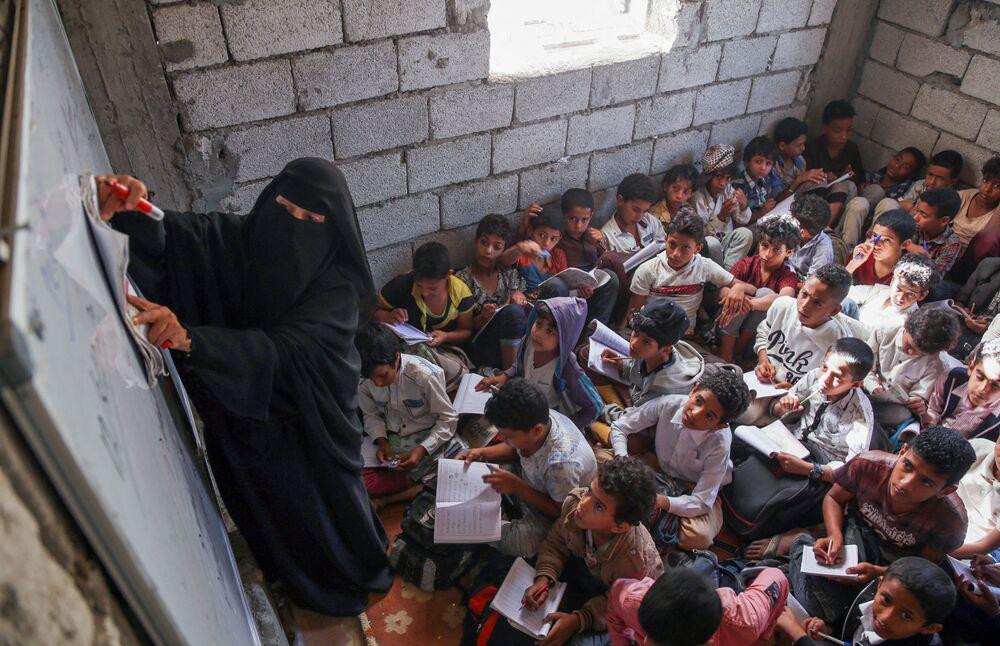 يحضر الطلاب اليمنيون دروسًا في مباني سكنية وتجارية غير مكتملة تم تحويلها إلى مدرسة وفصول دراسية في مدرسة الثلايا في مدينة تعز الثالثة في اليمن، 22 أغسطس 2021