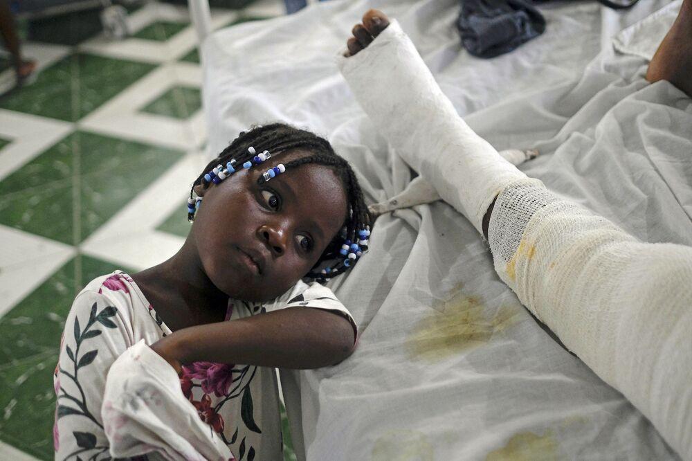 يونيكا ترقد بجانب والدتها جيرثا يليت، التي أصيبت في الزلزال قبل أسبوع واحد، في مستشفى الحبل بلا دنس، المعروف أيضًا باسم المستشفى العام في ليس كاي، هايتي، 22 أغسطس2021