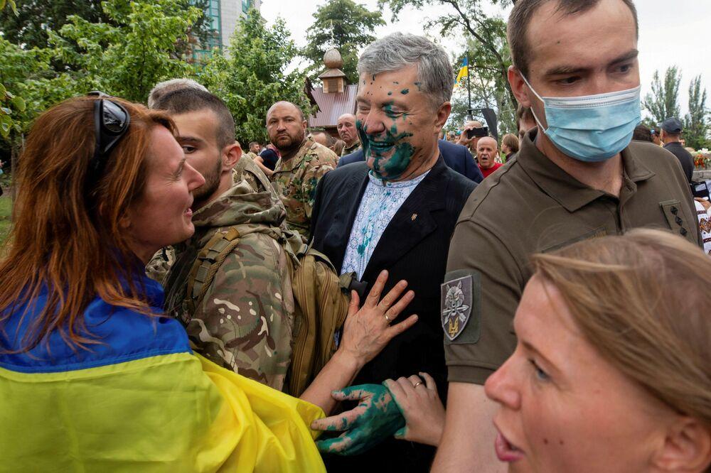 الرئيس الأوكراني السابق بيترو بوروشينكو يتحدث مع أحد أنصاره بعد أن رشه مهاجم بسائل أخضر خلال حدث بمناسبة عيد الاستقلال في كييف، أوكرانيا، 24 أغسطس 2021