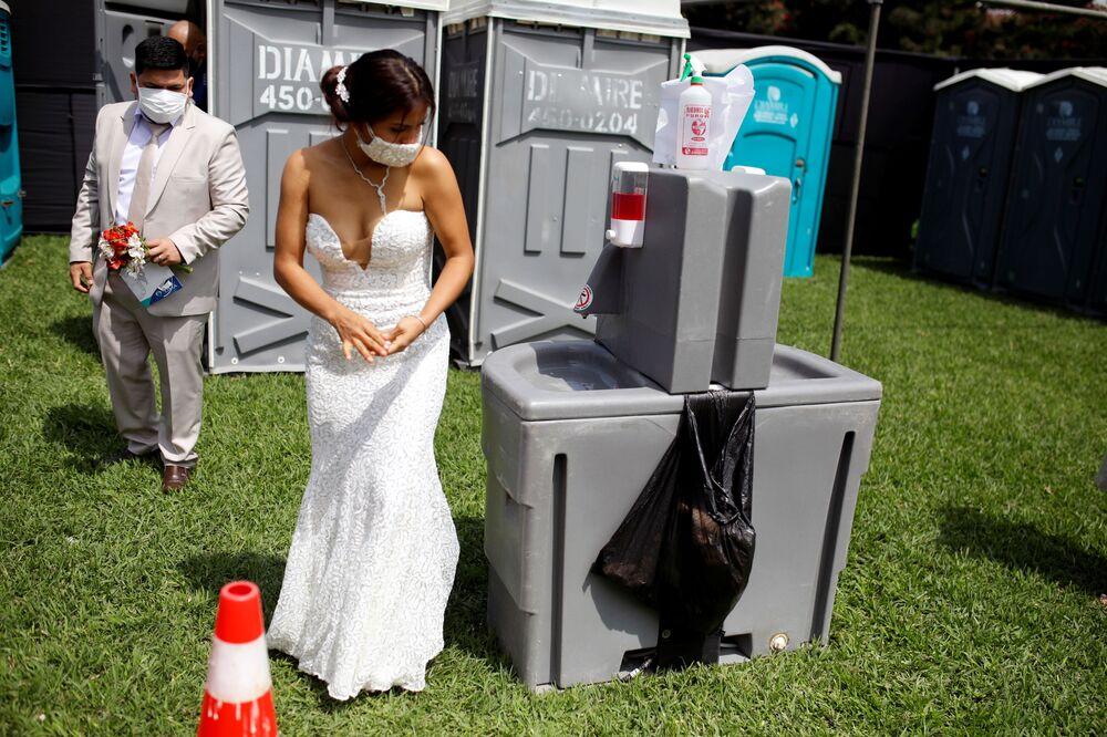 عروس تعقم يديها خلال أول حفل زفاف جماعي منذ ظهور جائحة فيروس كورونا (كوفيد-19) في ليما، بيرو  28 أغسطس 2021