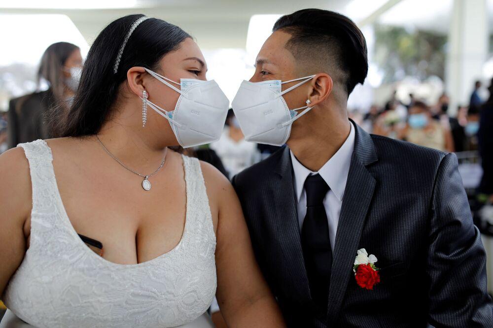 قبلة زوجين حديثين وهما يرتديان كمامة خلال أول حفل زفاف جماعي منذ ظهور جائحة فيروس كورونا (كوفيد-19) في ليما، بيرو  28 أغسطس 2021