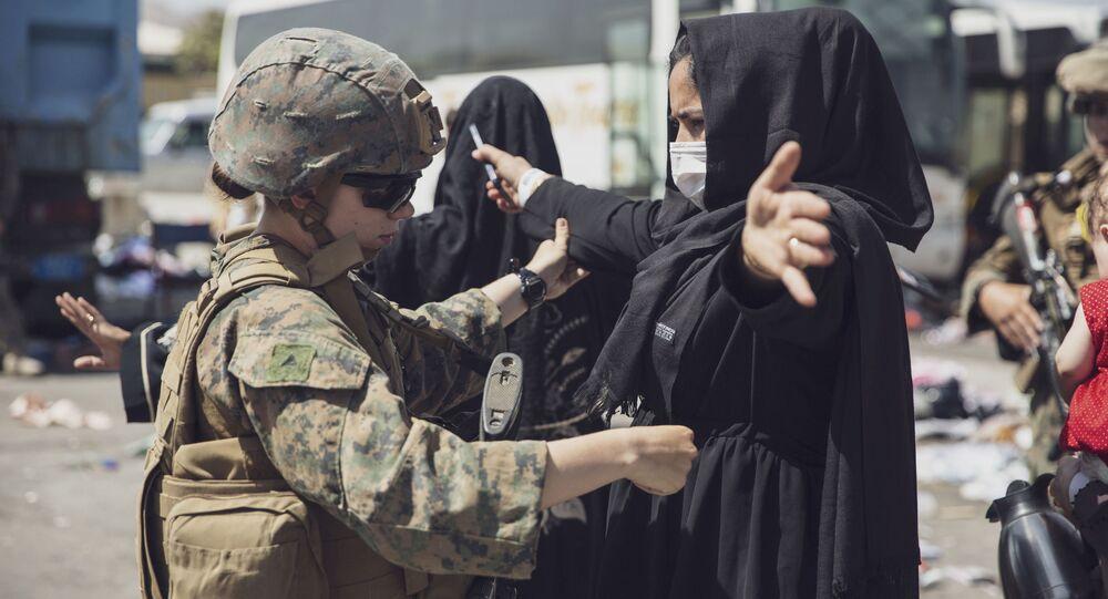 جندية أمريكية تقوم بفحص امرأة أفغانية قبل الإجلاء من مطار حامد كرزاي الدولي في كابول، أفغانستان 28 أغسطس 2021