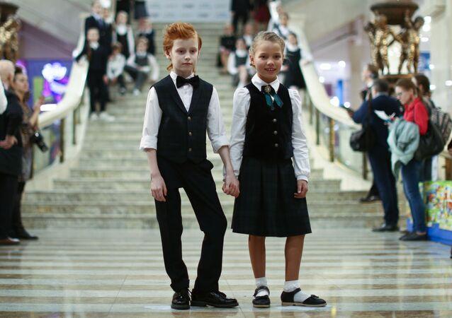 أطفال يعرضون نماذج من الزي المدرسي في افتتاح معرض لمصنعي الزي المدرسي في موسكو، في القاعة الرئيسية لمتجر الأطفال المركزي في ساحة لوبيانسكايا في موسكو 4 أبريل 2016