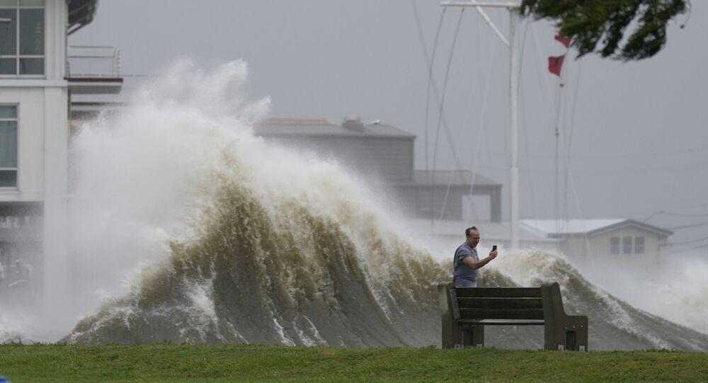 رجل يلتقط صوراً للأمواج العالية على طول شاطئ بحيرة بونتشارترين مع اقتراب إعصار إيدا، في نيو أورلينز 29 أغسطس 2021
