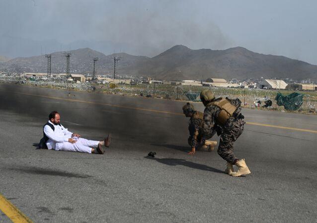 مقاتلو القوات الخاصة البدري التابعة لحركة طالبان (يمين) وصحفي ينهضون بعد أن سقطوا من سيارة في مطار كابول في 31 أغسطس 2021، بعد أن انسحاب قوات الولايات المتحدة من البلاد لإنهاء 20 عامًا. حرب بدأت وانتهت بوجود إسلامي متشدد في السلطة.
