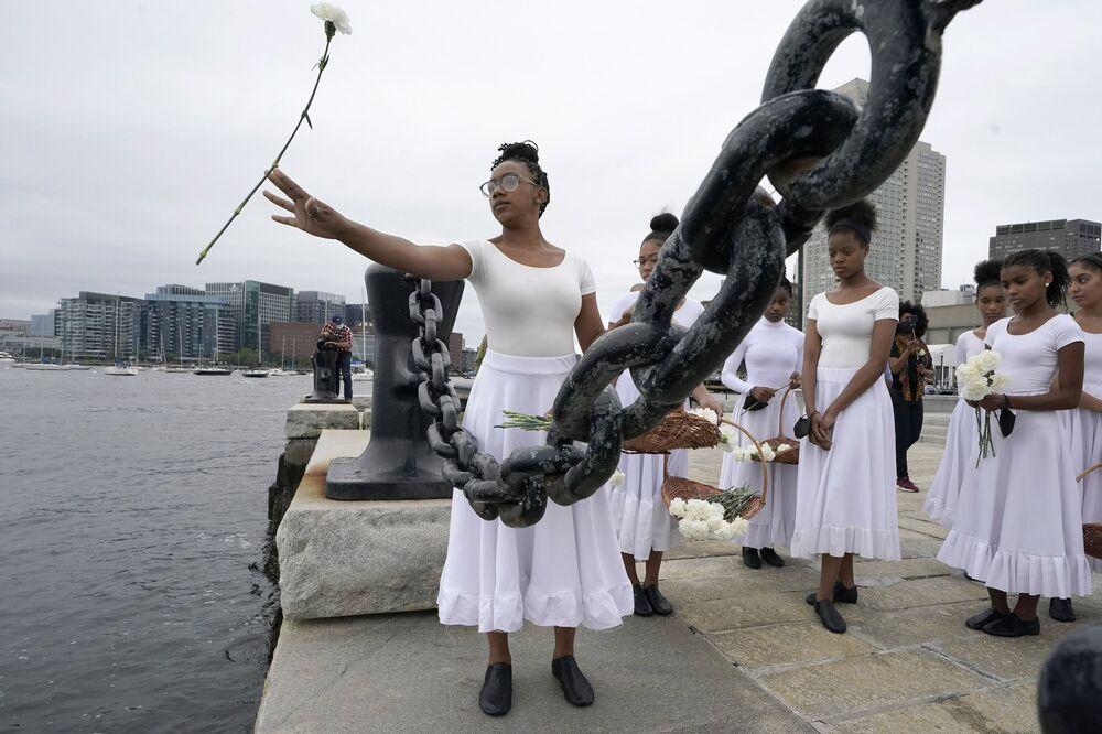 عضو في فرقة رقص Girlz of Imani التابعة لمركز OrigiNation الثقافي للفنون، يلقي القرنفل في ميناء بوسطن خلال حفل تكريمي لتاريخ العبودية في بوسطن، الولايات المتحدة 29 أغسطس 2021