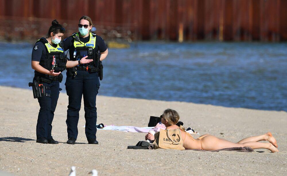 تتحدث الشرطة إلى امرأة تستمتع بطقس الربيع الدافئ بشكل غير معتاد على شاطئ سانت كيلدا في ملبورن،  حيث لا تزال المدينة مغلقة لأنها تكافح سلالة دلتا من فيروس كورونا، أستراليا 2 سبتمبر 2021