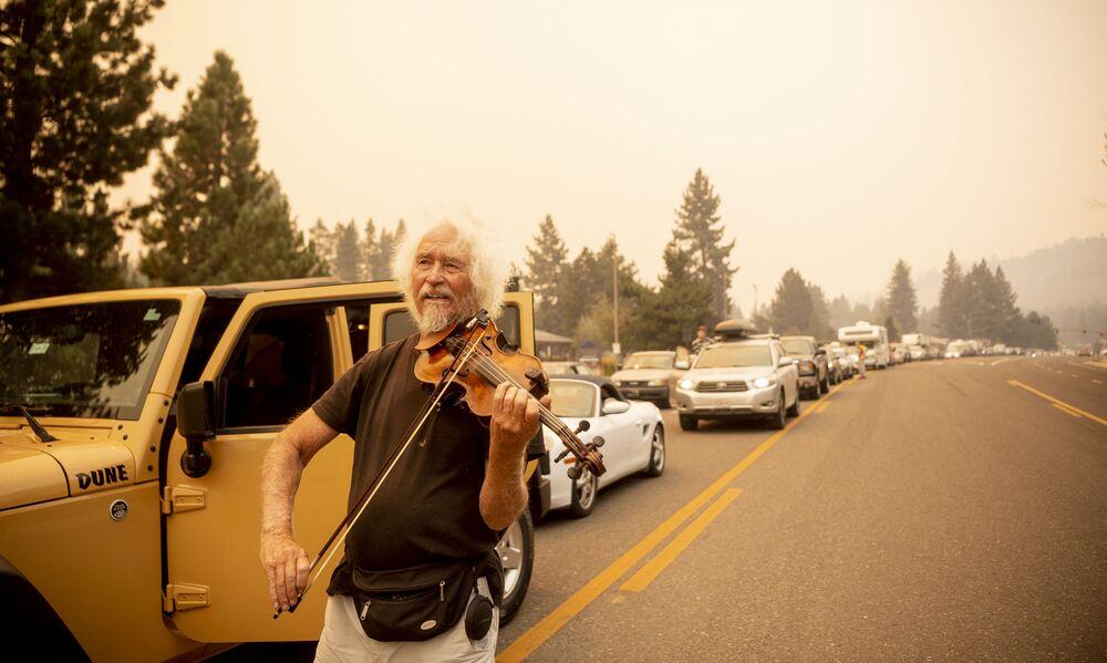 يعزف، ميل سموثرز، على الكمان بينما كان عالقًا في حركة المرور مع الأشخاص الذين تم إجلاؤهم من حريق كالدور في منطقة ساوث ليك تاهو، كاليفورنيا 30 أغسطس 2021