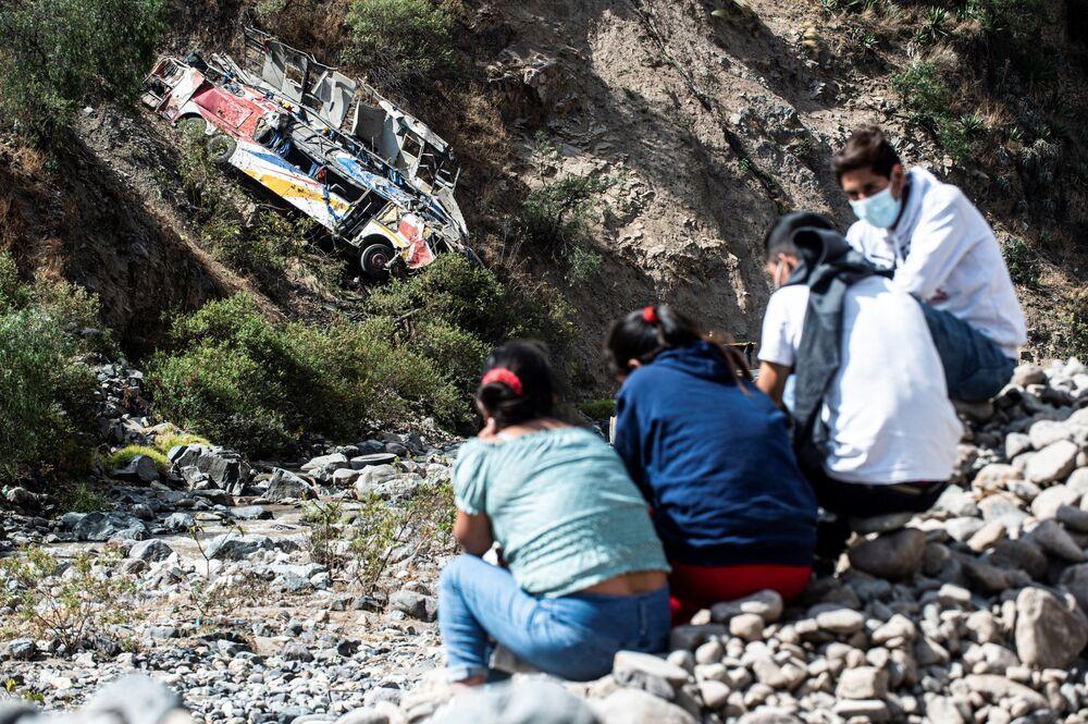 الناس يجلسون بالقرب من موقع التحطم بعد أن سقطت حافلة من جرف في ماتوكانا، شرق ليما، بيرو 31 أغسطس 2021
