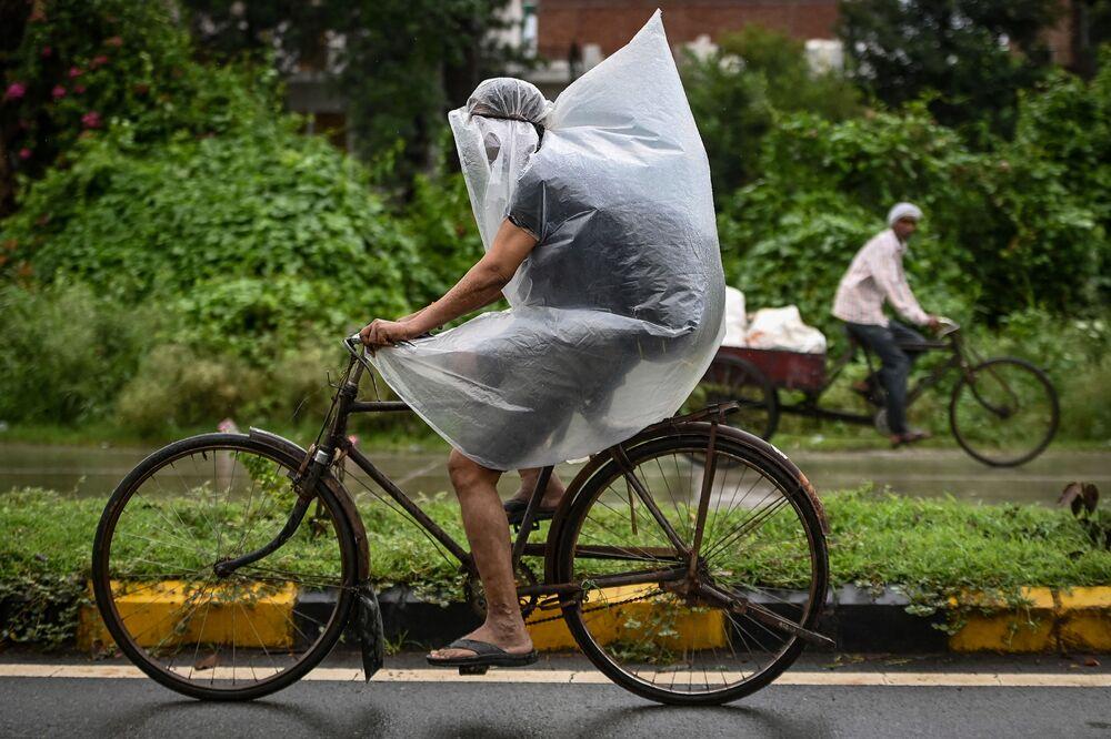 راكب دراجة يغطي نفسه بغطاء بلاستيكي أثناء هطول أمطار غزيرة في فريد آباد، الهند 1 سبتمبر 2021