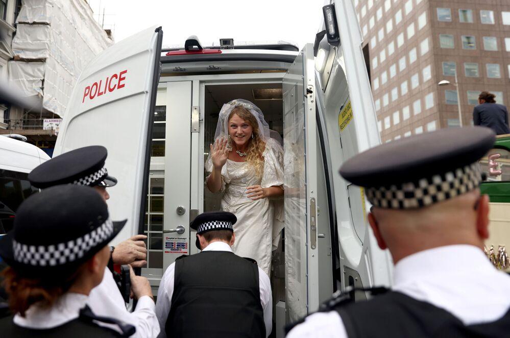 ناشطة ترتدي فستان زفاف وهي تقف في سيارة الشرطة خلال احتجاج تمرد الانقراض في لندن، بريطانيا، 31 أغسطس 2021