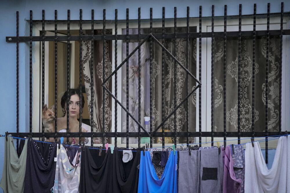شابة تشاهد عرضًا خارجيًا لـ أليكس فييا، في مسرحية You Did Not See Anything، التي تستكشف انتهاكات الشرطة ضد أفراد المجتمع الضعفاء، خلال Kathe، Akana! أو هنا والآن! مهرجان مسرح روما الدولي، خارج المجمعات السكنية في منطقة فقيرة بالعاصمة الرومانية بوخارست، رومانيا، 31 أغسطس 2021